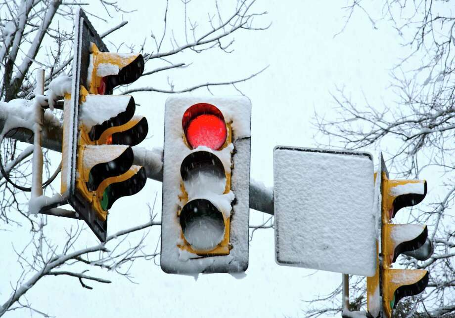 Heavy wet snow covers traffic signals at an intersection March 6, 2013 in Prince William County, Virginia. A winter storm is dumping rain, sleet and snow over the Washington, DC area, making driving treacherous. Photo: KAREN BLEIER, AFP/Getty Images / AFP