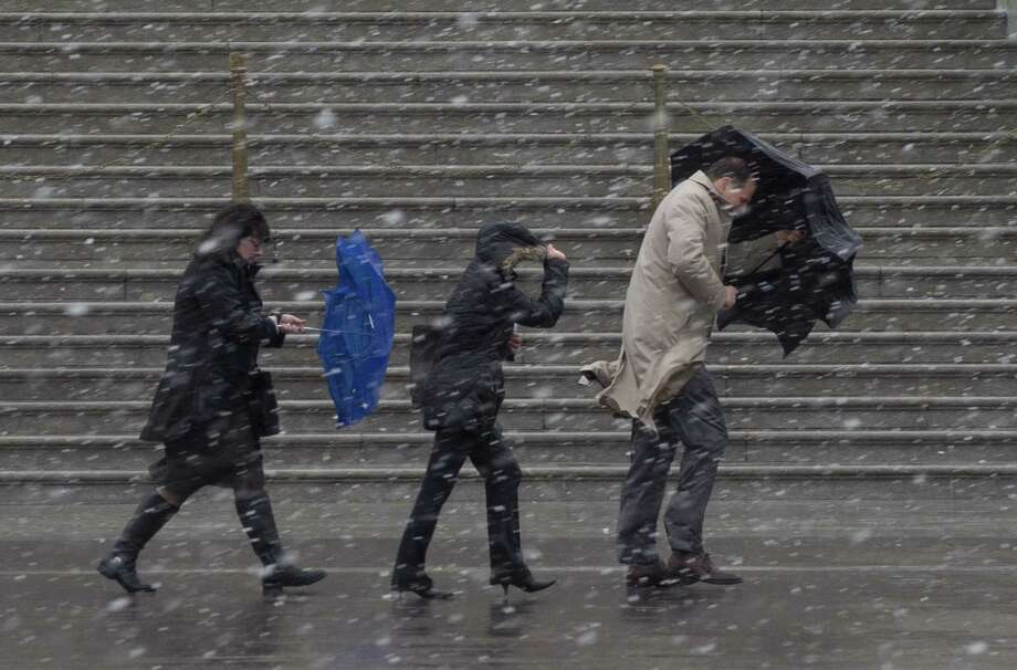 People walk as snow falls during a late winter storm at the US Capitol in Washington, DC, March 6, 2013. Federal offices and many schools have closed in preparation for a mix of snow, sleet and rain which could account for the area's largest winter storm in two years. Photo: SAUL LOEB, AFP/Getty Images / AFP