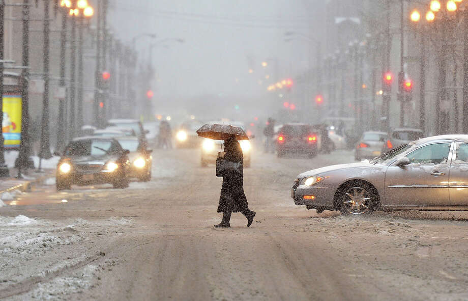A pedestrian crosses the street as snow falls on March 5, 2013 in Chicago, Illinois. The worst winter storm of the season is expected to dump 7-10 inches of snow on the Chicago area with the worst expected for the evening commute. Photo: Brian Kersey, Getty Images / 2013 Getty Images
