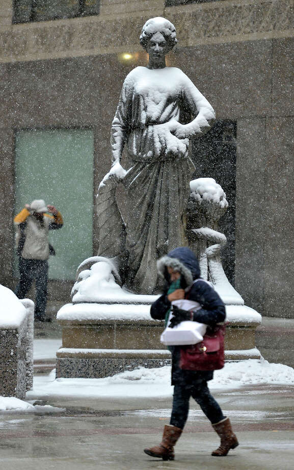 A pedestrian walks by a snow-covered statue in front of the Chicago Board of Trade on March 5, 2013 in Chicago, Illinois. The worst winter storm of the season is expected to dump 7-10 inches of snow on the Chicago area with the worst expected for the evening commute. Photo: Brian Kersey, Getty Images / 2013 Getty Images