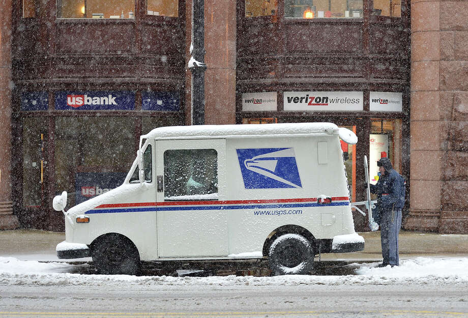 A mail carrier loads his truck on March 5, 2013 in Chicago, Illinois. The worst winter storm of the season is expected to dump 7-10 inches of snow on the Chicago area with the worst expected for the evening commute. Photo: Brian Kersey, Getty Images / 2013 Getty Images