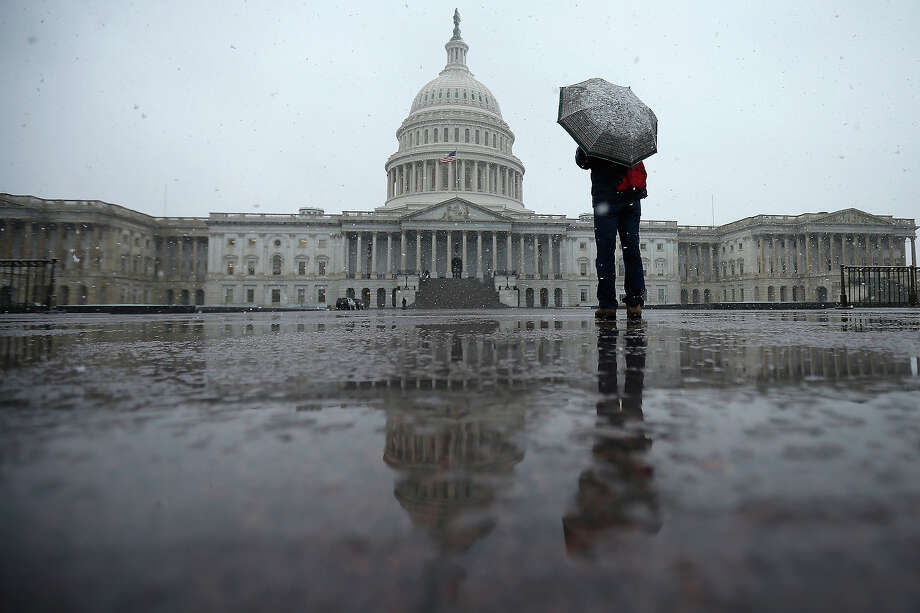 A tourist takes cover underneath an umbrella while snapping a photo of the U.S. Capitol as snow and rain falls March 6, 2013 in Washington, DC. A late winter storm is expected to cover the Mid-Atlantic region after dropping almost a foot of snow across the the West and Midwest. Photo: Chip Somodevilla, Getty Images / 2013 Getty Images