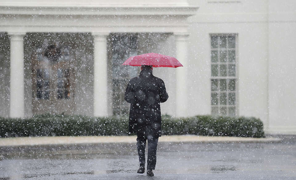 A White House staffer walks to the West Wing during a snow storm at the White House March 6, 2013 in