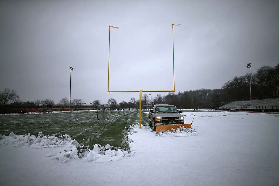 A grounds crew truck plows snow off the football field at Catholic University on March 6, 2013 in Washington, DC.  A late-season winter snowstorm is forecasted to hit the Washington area and is expected to dump 5 to 10 inches of snow. Photo: Mark Wilson, Getty Images / 2013 Getty Images