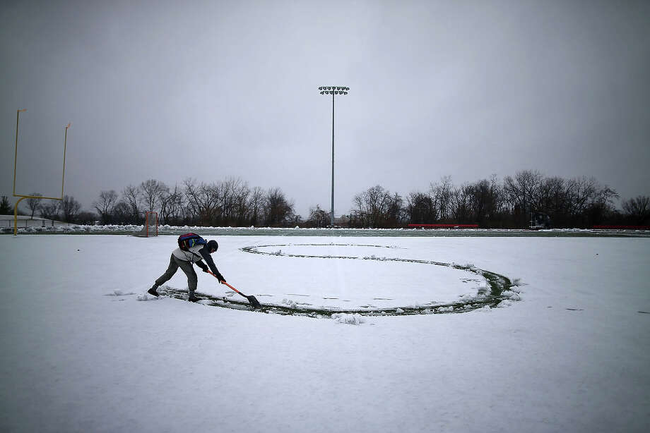 Student Hunter Gallagher uses a shovel to write a letter from his girlfriends name in the snow on the football field at Catholic University on March 6, 2013 in Washington, DC.  A late-season winter snowstorm is forecasted to hit the Washington area and is expected to dump 5 to 10 inches of snow. Photo: Mark Wilson, Getty Images / 2013 Getty Images