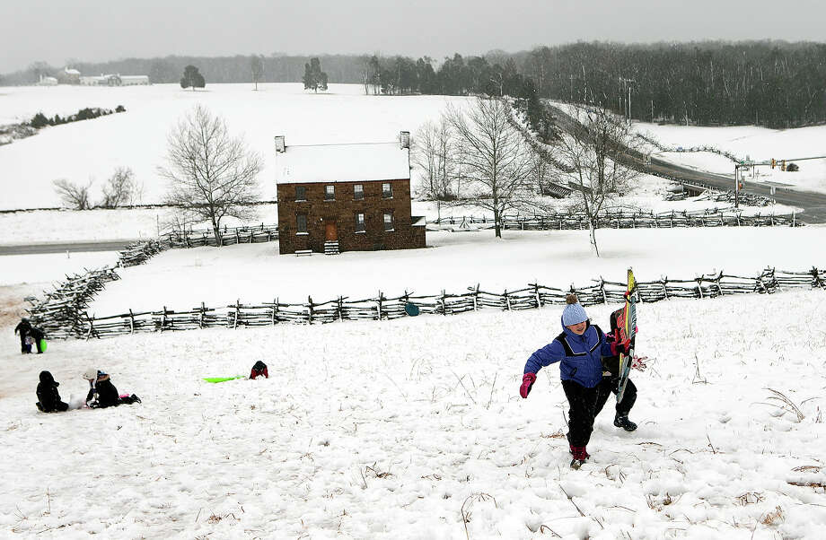 Annie Castro (L) and Sophia Benedetto battle gusting winds and snow to reach the top of a sledding hill on the grounds of Manassas Battlefield Park March 6, 2013 in Manassas, Virginia. A winter storm hit the Washington, DC area today with areas west of the city seeing significant snowfall, but the city itself seeing minimal snow. Photo: Win McNamee, Getty Images / 2013 Getty Images