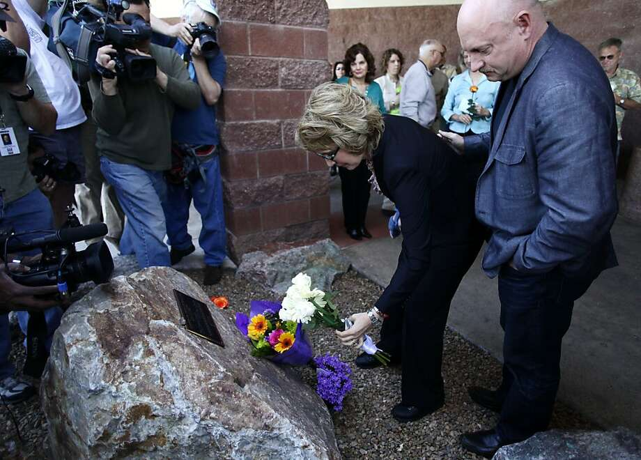 TUCSON, AZ - MARCH 06: Former Congresswoman Gabby Giffords places flowers at a memorial with her husband Mark Kelly before they attend a news conference asking Congress and the Senate to provide stricter gun control in the United States on March 6, 2013 in Tucson, Arizona. Giffords and Kelly were joined by survivors of the Tucson shooting as they spoke outside the Safeway grocery store where the shooting happened two years ago where six people were killed.  (Photo by Joshua Lott/Getty Images) Photo: Joshua Lott, Getty Images
