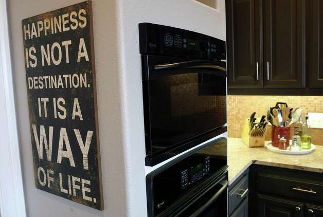 Carey Morgan's kitchen is decorated with a sign she found in a local boutique that described her thoughts. Photo: Cynthia Esparza, San Antonio Express-News / San Antonio Express-News