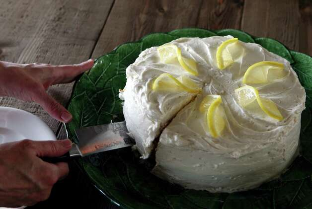 Carey Morgan cuts a piece of the  Limoncello cake she made in her Inwood home. Photo: Cynthia Esparza, San Antonio Express-News / San Antonio Express-News