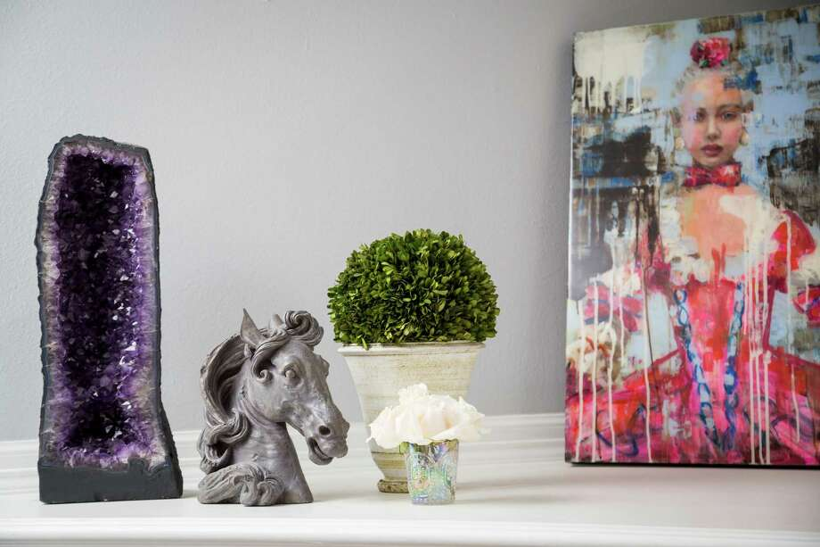 On top of the fireplace is an amethyst geode from Brazil, a horsehead paperweight, plants brought from Los Angeles and a painting by Rimi Yang. ( Michael Paulsen / Houston Chronicle ) Photo: Michael Paulsen, Staff / © 2013 Houston Chronicle