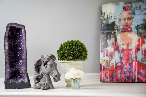 On top of the fireplace is an amethyst geode from Brazil, a horsehead paperweight, plants brought from Los Angeles and a painting by Rimi Yang. ( Michael Paulsen / Houston Chronicle )