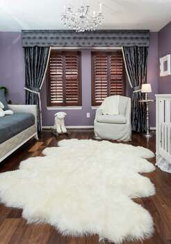 The vintage purple walls in the nursery are set off by slate blue curtains from Glick Textiles lined in Houlet pom-poms and a sheepskin rug. Photo: Michael Paulsen, Staff / © 2013 Houston Chronicle