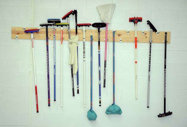 Brooms hang on the wall available to new curlers Tuesday, Feb. 26, 2013 at the Nutmeg Curling Club in Bridgeport, Conn. Photo: Autumn Driscoll / Connecticut Post