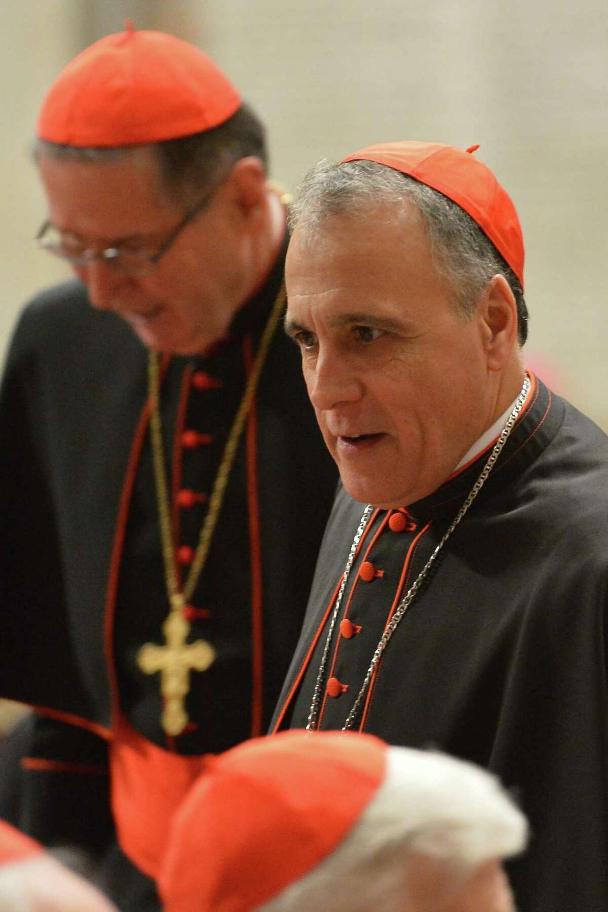 Cardinals Daniel DiNardo, right, and Roger Mahony take place for a prayer with other cardinals on Wednesday. DiNardo's briefings have been ended.