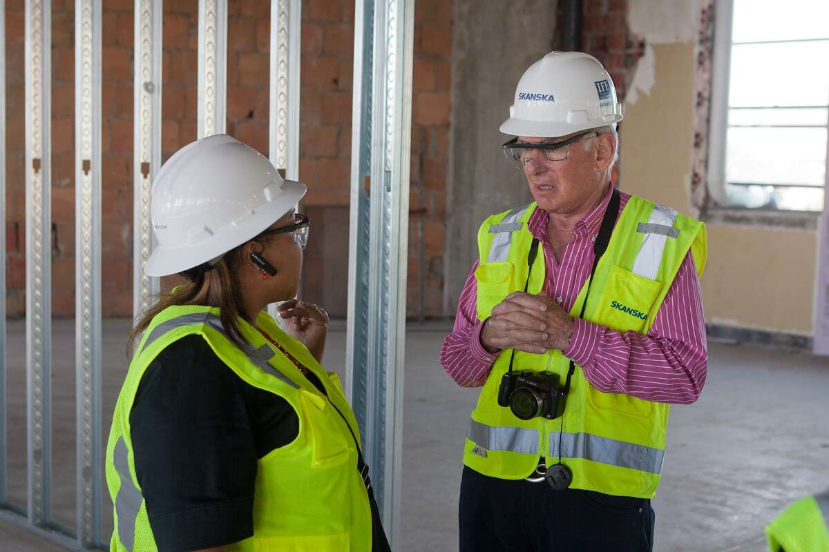 Brenda Prejean and Alan Finger discuss several historical artifacts during a tour of the HCC Central Campus main building, the old San Jacinto High School, which is being rebuilt.
