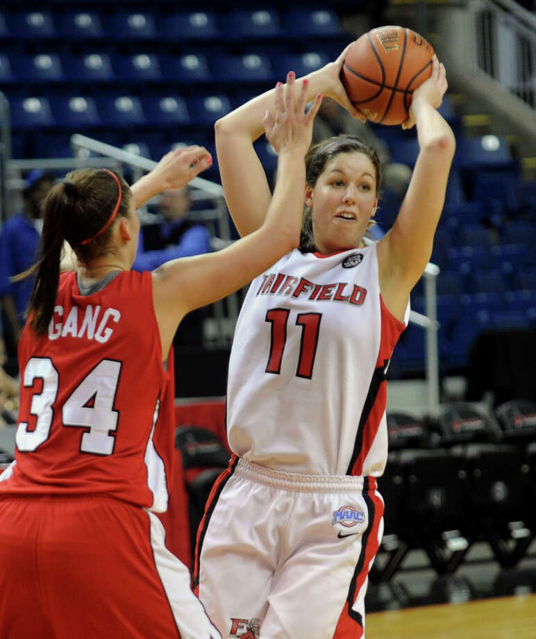 Fairfield University's #11 Brittany MacFarlane looks to pass the ball, during womens basketball action against Marist at the Webster Bank Arena in Bridgeport, Conn. on Thursday January 12, 2012. At left is Marist's #34 Brandy Gang. Photo: Christian Abraham / Connecticut Post