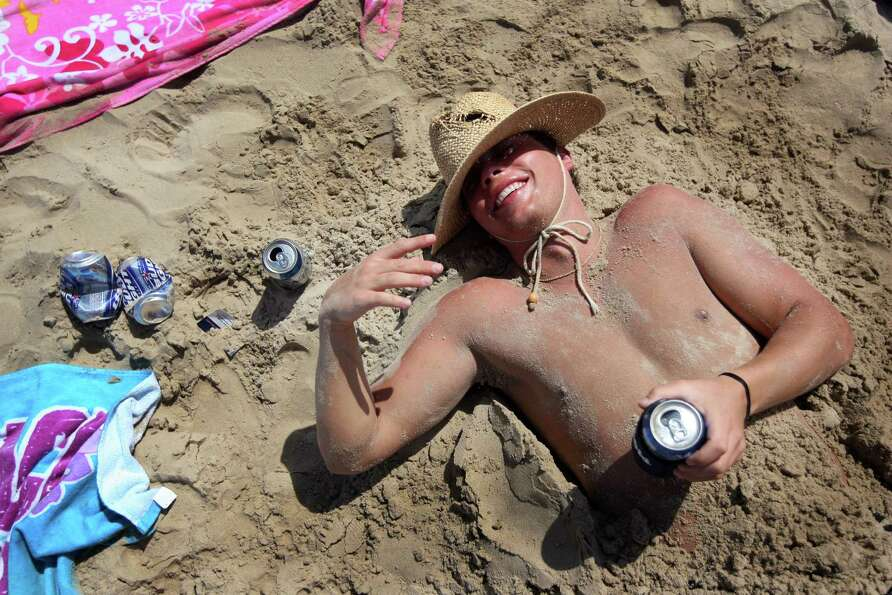 A drunken student lies half buried in sand on the beach during the annual ritual of Spring Break in