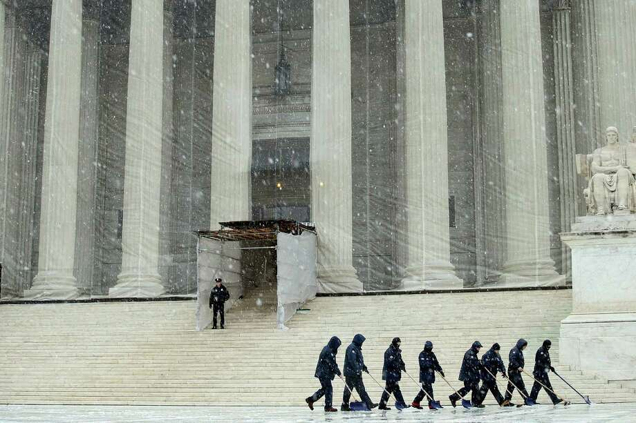 Workers use shovels and brooms to remove a heavy mixture of snow and ice from the west front of the U.S. Supreme Court March 6, 2013 in Washington, DC. A late winter storm is expected to cover the Mid-Atlantic region after dropping almost a foot of snow across the the West and Midwest. Photo: Chip Somodevilla, Getty Images / 2013 Getty Images