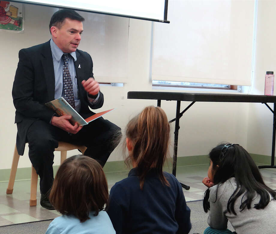 Police Chief Gary McNamara reads to children at World Read Aloud Day program Wednesday at the Fairfield Public Library.  FAIRFIELD CITIZEN, CT 3/6/13 Photo: Mike Lauterborn / Fairfield Citizen contributed