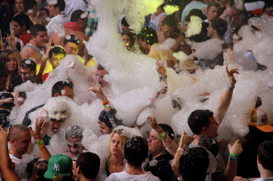 Spring Break revelers enjoy a foam party at a nightclub in the resort city of Cancun on Monday. (AP Photo Israel Leal) Photo: Multiple