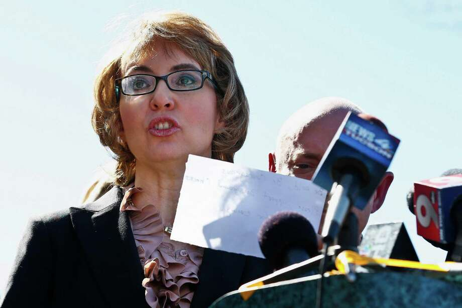 Former Rep. Gabrielle Giffords, left, reads a statement as she and husband Mark Kelly, right, returned to the site of a shooting that left her critically wounded to urge key senators to support expanded background checks for gun purchases, Wednesday, March 6, 2013, in Tucson, Ariz. (AP Photo/Ross D. Franklin) Photo: Ross D. Franklin