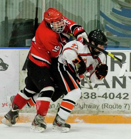 Greenwich High School's Paul MacKen and Ridgefield High School's Ian Ball tangle  during the Division I boys ice hockey playoffs at Ridgefield. Mar. 6, 2013 Photo: Scott Mullin / The News-Times Freelance