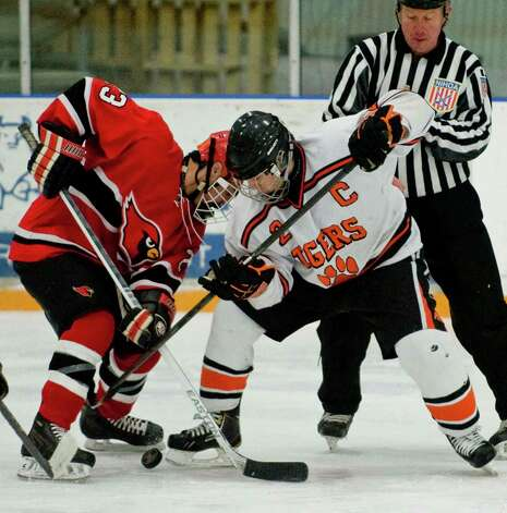 Greenwich High School's Matt Lodato and Ridgefield High School's Vincent Rella fight for the loose puck in the Division I boys ice hockey playoffs played at Ridgefield. Mar. 6, 2013 Photo: Scott Mullin / The News-Times Freelance