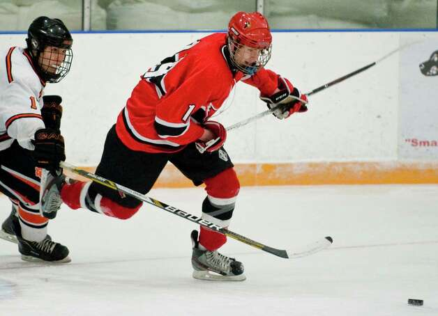 Greenwich High School's Jack Corrigan chases the loose puck during the Division I boys ice hockey playoffs against Ridgefield High School, played at Ridgefield. Mar. 6, 2013 Photo: Scott Mullin
