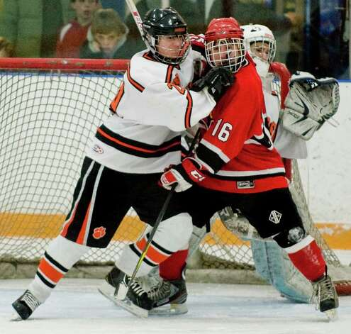 Ridgefield High School's Geoffrey Schneider and Greenwich High School's Paul MacKen push in front of the net during the Division I boys ice hockey playoffs at Ridgefield. Mar. 6, 2013 Photo: Scott Mullin / The News-Times Freelance