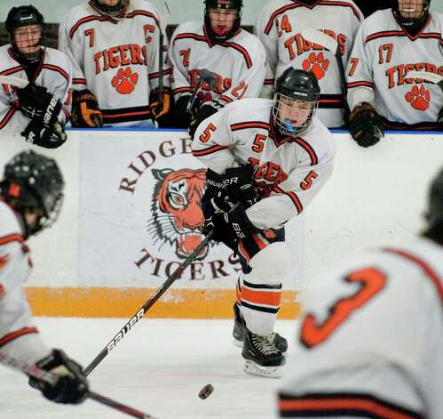 Ridgefield High School's Alex Rowella picks up the puck near center ice during the Division I boys ice hockey playoffs against Greenwich High School, played at Ridgefield. Mar. 6, 2013 Photo: Scott Mullin / The News-Times Freelance