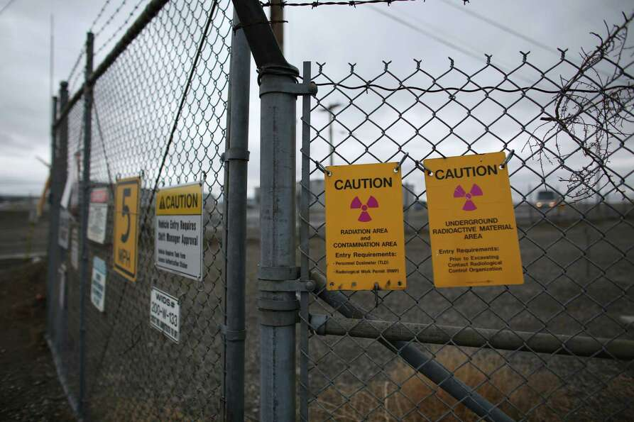 Signs warn of a contaminated area at a tank