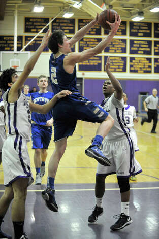 Newtown's Connor Quinn shoots while under pressure from Westhill's Evan Skoparantzas, left, and Guyveson Cassamajor during their game at Westhill High School on Wednesday, March 6, 2013. Westhill won, 56-34. Photo: Jason Rearick / The Advocate