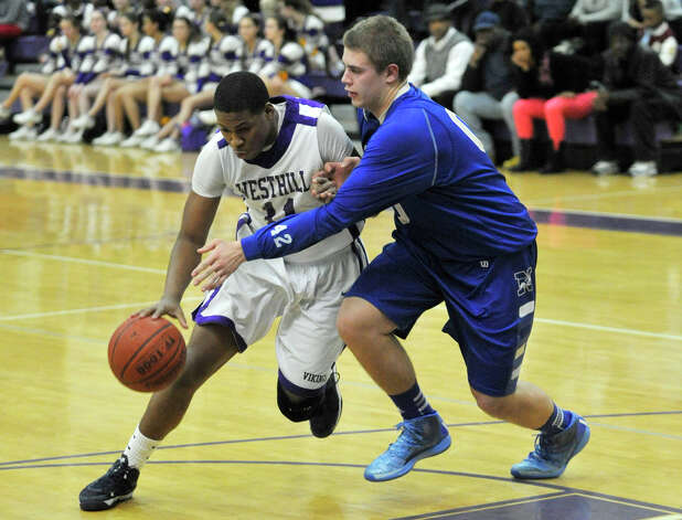 Westhill's Guyveson Cassamajor drives to the basket around Newtown's Julian Dunn during their game at Westhill High School on Wednesday, March 6, 2013. Westhill won, 56-34. Photo: Jason Rearick / The Advocate