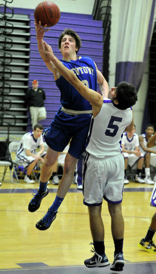Newtown's Connor Quinn shoots while under pressure from Westhill's Evan Skoparantzas during their game at Westhill High School on Wednesday, March 6, 2013. Westhill won, 56-34. Photo: Jason Rearick / The Advocate