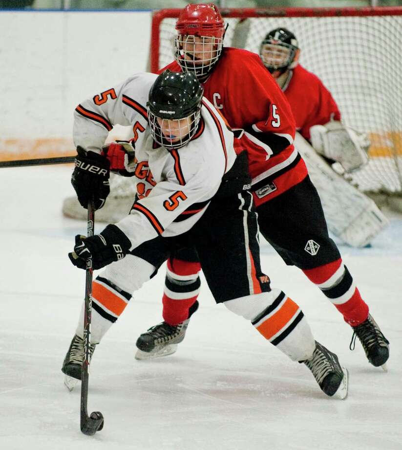 Ridgefield High School's Alex Rowella tries to manuver the puck away from Greenwich High School's Reed Brady during the division I boys ice hockey playoffs at Ridgefield. Mar. 6, 2013 Photo: Scott Mullin