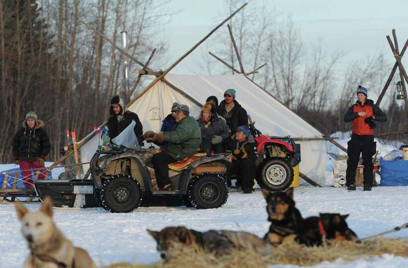 People from the Athabaskan village of Nikolai, Alaska, take a look at the Iditarod sled dog teams pa