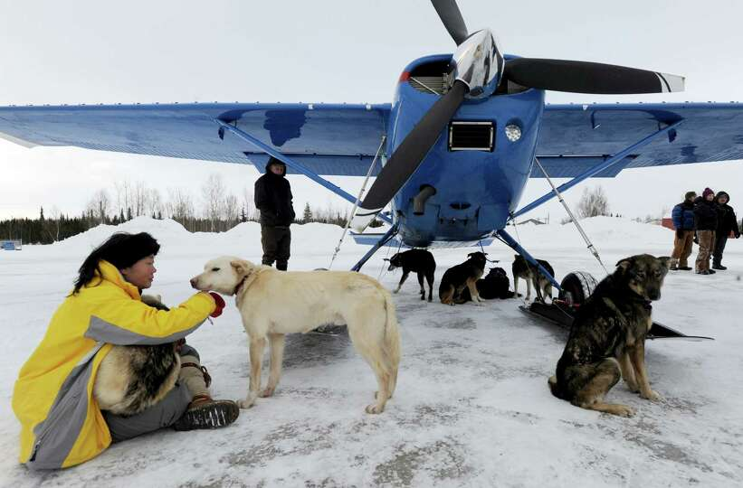 Kidron Flynn sits with dropped dogs getting ready to be loaded in an Iditarod Air Force plane during