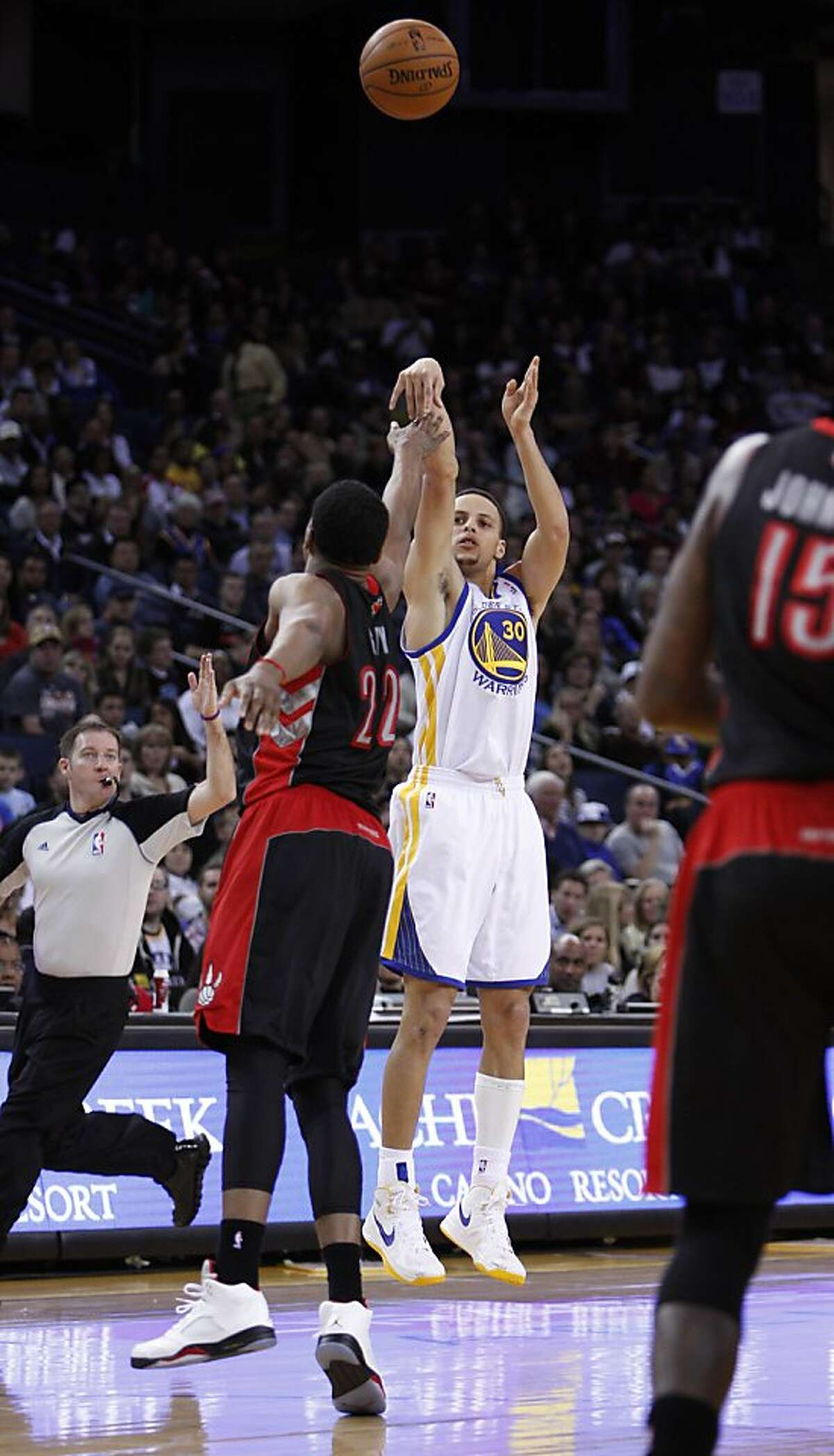 Stephen Curry (30) puts up a shot as he's guarded by Rudy Gay (22) in the second half. The Golden State Warriors played the Toronto Raptors at Oracle Arena in Oakland, Calif., on Monday, March 4, 2013.