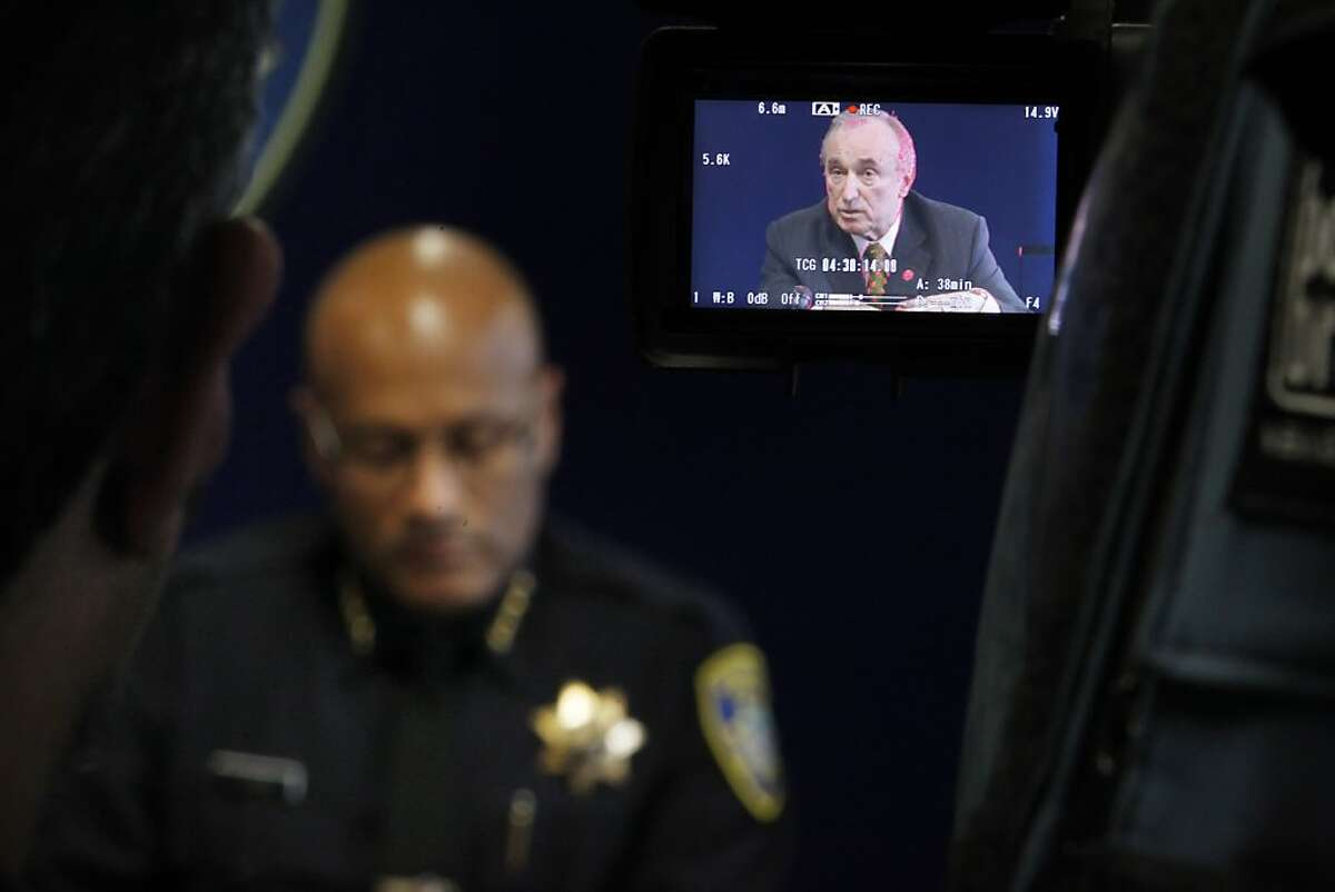 Oakland Police Chief Howard Jordan listens as consultant William Bratton, in camera screen, speaks to the media about new strategies for policing in Oakland, Calif, on Wednesday, March 6, 2013, hours before a public forum at the Oakland Police Advisory Board.