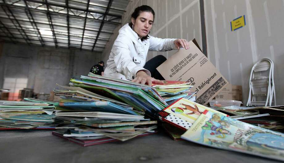 Guadalupe Harper helps box up books for the nonprofit project Books Between Kids, which was started by two River Oaks moms and has ballooned from there. Photo: Karen Warren, Staff / © 2013 Houston Chronicle
