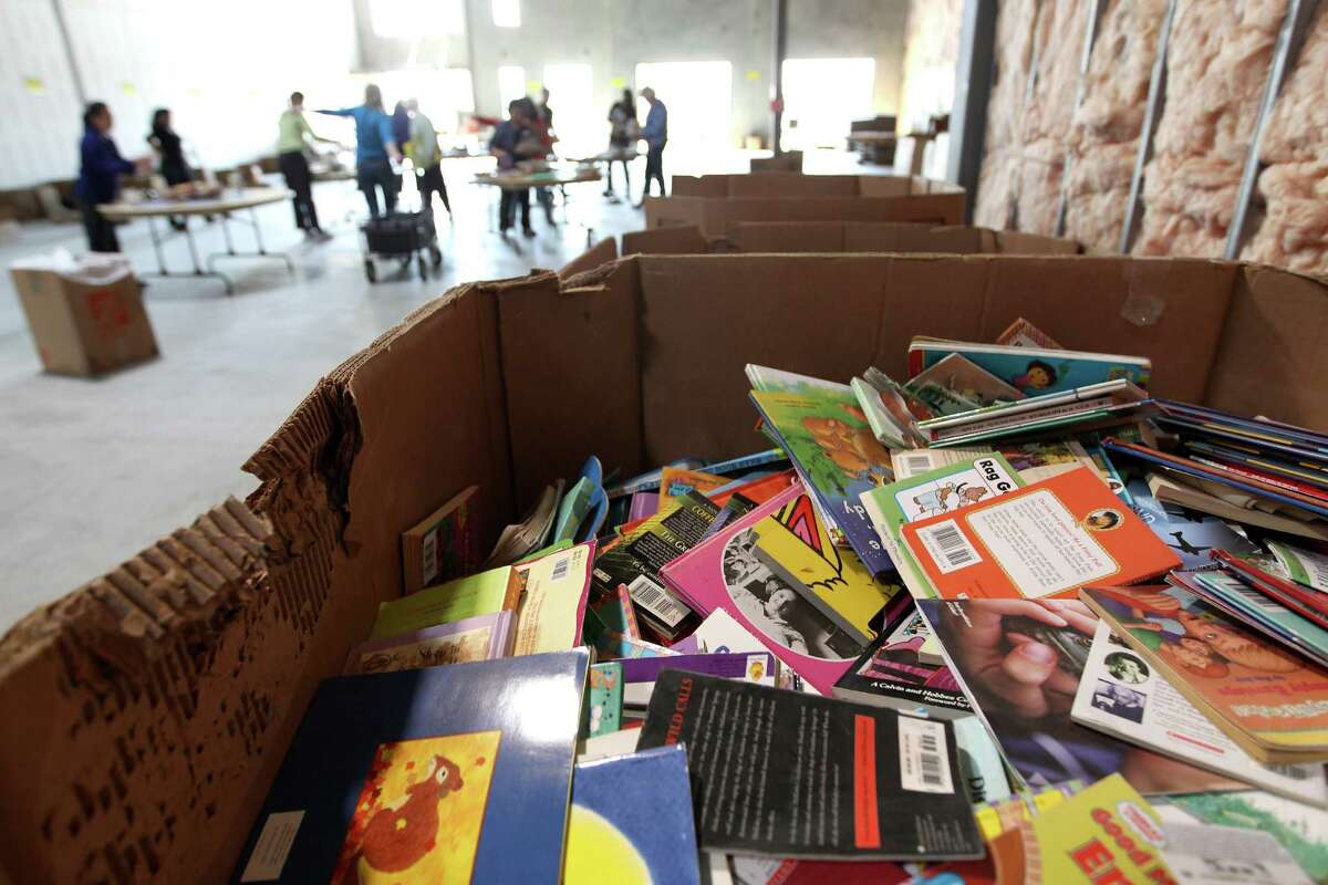 Gently used books wait to be sifted through by volunteers. The nearly 70,000 books will then be given to selected Houston ISD underprivileged students.