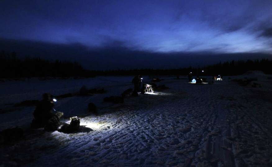 Headlamps provide light for mushers and veterinarians working with sled dogs in the village of Nikol