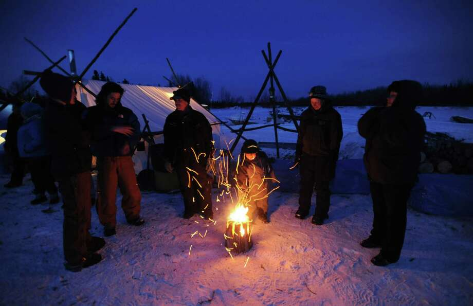 Four-year-old Kayden Alexie pokes a fire with a stick as people gather in the village of Nikolai, Alaska, to watch and help with dog teams pulling into the checkpoint during the Iditarod Trail Sled Dog Race, Tuesday, March 5, 2013. Photo: Bill Roth, Associated Press / Anchorage Daily News