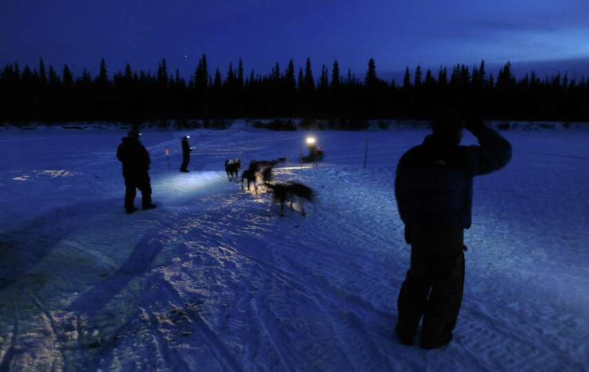 Volunteers wait for Aaron Peck to pull into the checkpoint in the village of Nikolai, Alaska during