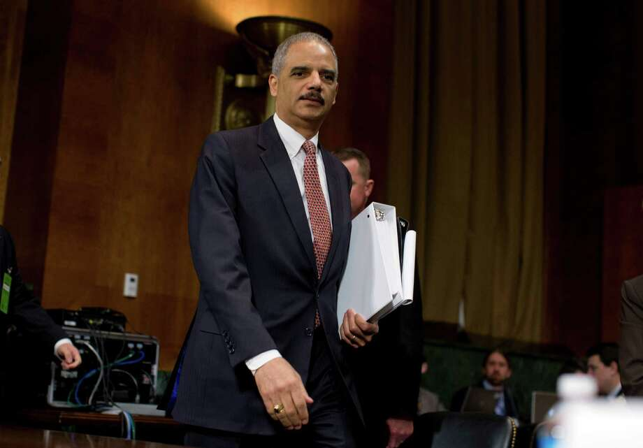 """Attorney General Eric Holder arrives on Capitol Hill in Washington, Wednesday, March 6, 2013, to testify before the Senate Judiciary Committee hearing: """"Oversight of the U.S. Department of Justice."""" Holder urged Congress to confront gun violence by requiring universal background checks, imposing tougher penalties on traffickers and banning high-capacity magazines and military-style assault weapons.  (AP Photo/Evan Vucci) Photo: Evan Vucci"""