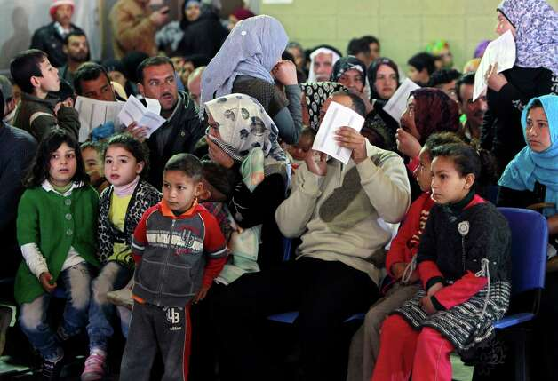 "Syrian families wait their turn to register at the UNHCR center in the northern city of Tripoli, Lebanon, Wednesday, March. 6, 2013.  The number of Syrians who have fled their war-ravaged country and are seeking assistance has now topped the one million mark, the United Nations' refugee agency said Wednesday warning that Syria is heading towards a ""full-scale disaster."" (AP Photo/Bilal Hussein) Photo: Bilal Hussein"
