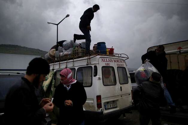 FILE - In this Thursday, Dec. 20, 2012 file photo, Syrian refugees,who fled their home in Idlib due to a government airstrike load their belongings into a vehicle just after crossing the border from Syria to Turkey, in Cilvegozu, Turkey.  Turkey is home to nearly 200,000 Syrian refugees in camps, with another 100,000 living on their own. The Turkish government has been funding and managing the refugees, whom they have sheltered in 17 camps that have schools, medical centers and other social facilities. (AP Photo/Muhammed Muheisen, File) Photo: Muhammed Muheisen