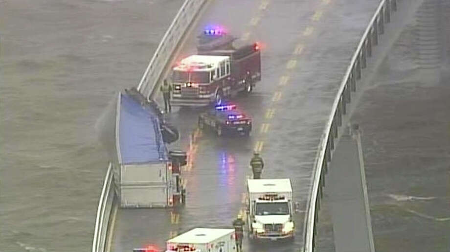 In this image from video provided by WJZ-TV, emergency crews surround a tractor-trailer that overturned on the westbound span of the Bay Bridge, which crosses the Chesapeake Bay in Maryland. The bridge was closed in both directions after the crash Wednesday afternoon due to high winds from a snowstorm blowing through the Mid-Atlantic region. (AP Photo/WJZ-TV) Photo: WJZ-TV
