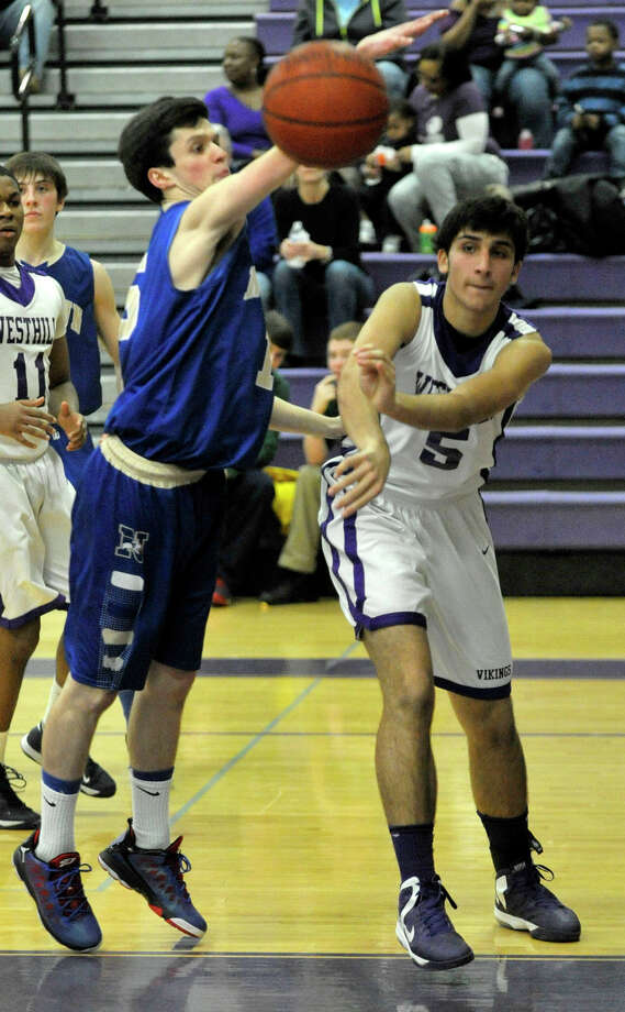 Westhill's Evan Skoparantzas passes the ball while under pressure from Newtown's Gavin Scallon during their game at Westhill High School on Wednesday, March 6, 2013. Photo: Jason Rearick / The Advocate