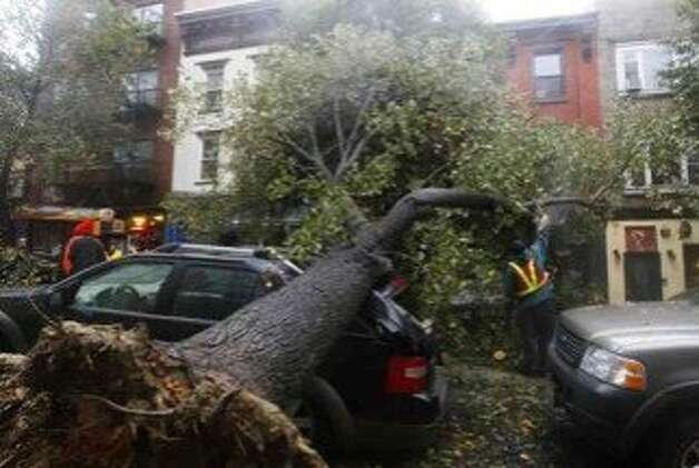 A workman cuts a tree in pieces after it fell on top of a car in Hoboken, New Jersey, October 29, 2012. Hurricane Sandy, one of the biggest storms ever to hit the United States, battered the densely populated East Coast, shutting down transportation, forcing evacuations in flood-prone areas and interrupting the presidential election campaign. Photo: Gary Hershorn, REUTERS